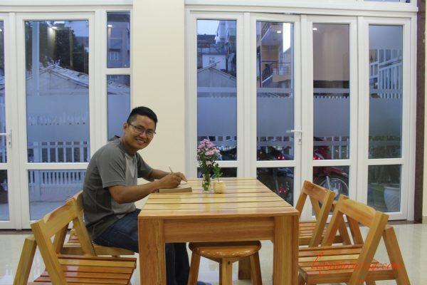 Chiếc bàn giữa phòng khách 4 quarters homestay Đà Lạt, nơi luôn có hoa tươi và cuốn sổ nhỏ để bạn ghi lưu bút.